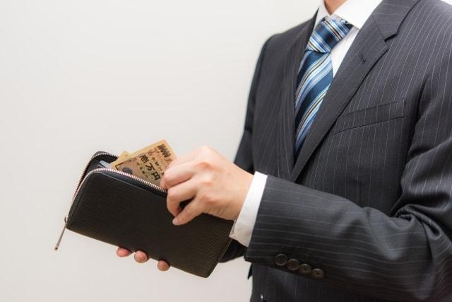 女性に投資する男性が財布を開いている様子。裏切られた後に思い出している。