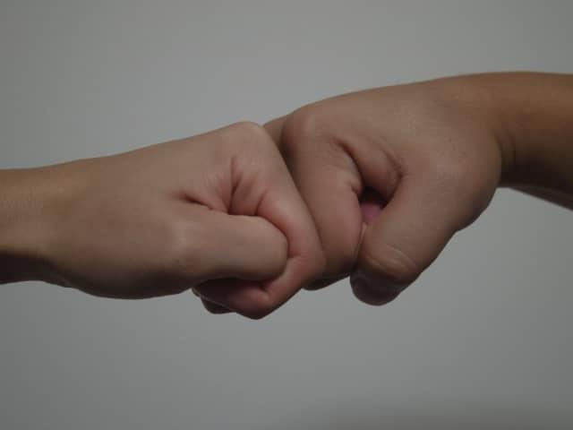 手をつなぐのが嫌いな心理を象徴した「こぶし」を合わせるカップルの手