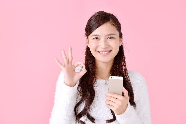 2回目のデートの誘い方を知って自信を付けた女性が手でOKマークを作っている。