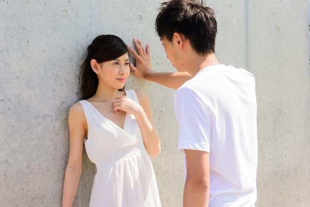 ベタな恋愛テクニックを使う男性。男性が女性に壁ドンをしている様子。