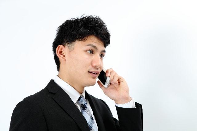 20代で年収1000万円の男性が携帯で電話している様子。