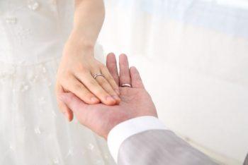 結婚したいか結婚したくないか関わらず、幸せな結婚をイメージした画像。新郎と新婦が手を取り合っている。お互いの手には結婚指輪が光る。