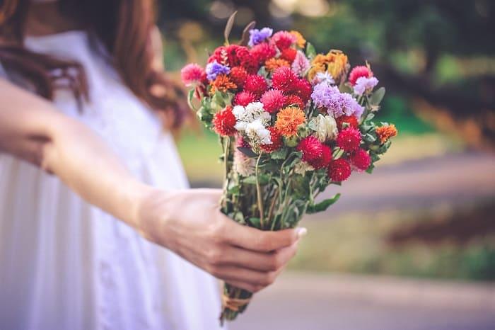 すごく奥手な女性が気持ちを表現するために花束を差し出している様子