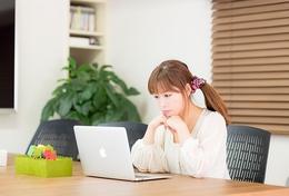 年下の女性がパソコンで恋愛のことを調べている様子