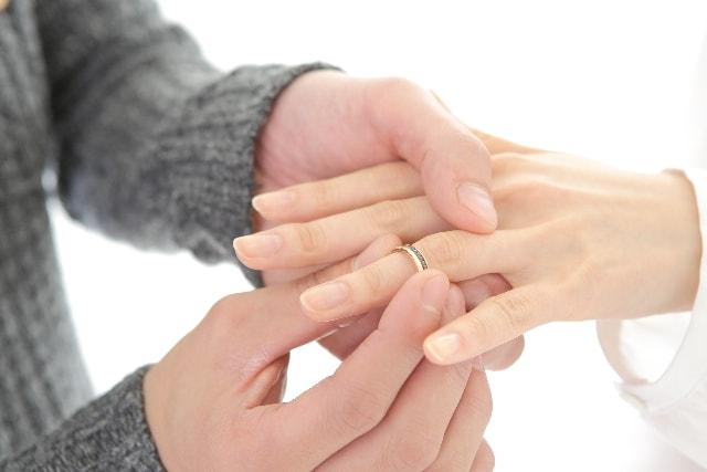 彼氏が彼女に指輪のプレゼントをしている様子