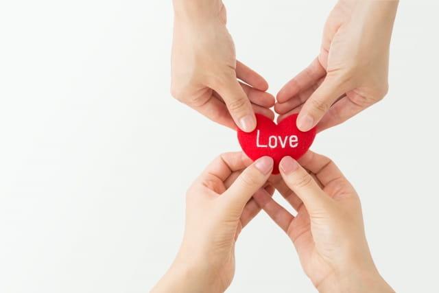 恋に恋する人の恋愛傾向をイメージした「ハートを手渡す女性」の画像。
