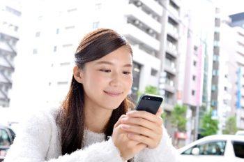 LINEで好きな人の気持ちを知りたい女性が携帯を見ているところ