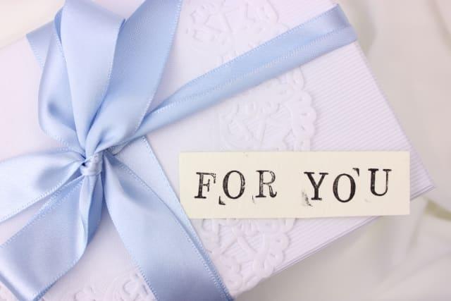 彼氏から指輪をプレゼントされる時期やタイミングから意味を考える女子が見つめる小包