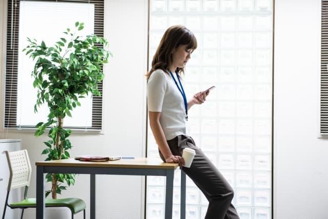 職場にいる好きな人にお土産を渡したい女性が渡し方を考えている。