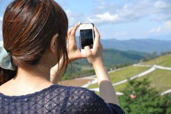 好きな人とLINEするために、画像を取る女性。珍しい景色を送って、好きな人との会話につなげる。