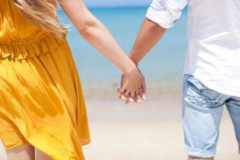 3回目のデートが脈ありかわかる瞬間。夏のデート中に海で手をつないだまだ付き合う前の男女の画像。