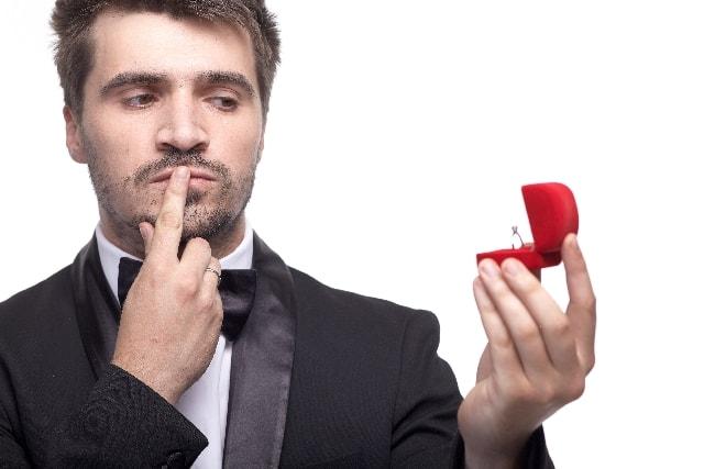 いきなり告白すると相手はどう思うのか、指輪を見ながら考える男性の画像。