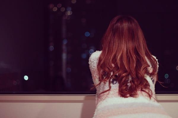 彼氏に飽きた女性が夜に窓の外見ながら悩む様子。