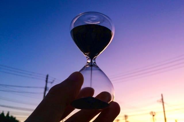 女友達から好きな人に変わる期間を心配している女性が見つめる砂時計