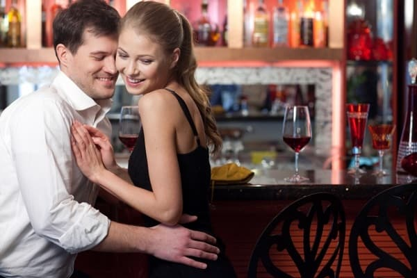 お酒に酔った男性が遊びの女性と飲んでいる様子。本命の女性とは違う態度を取っている。