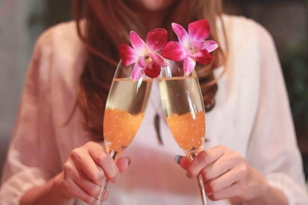女性が目の前の男性を意識した時の気持ちを表現した「2個のグラスをくっつける女性」の画像。
