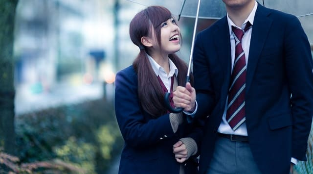 笑顔で好きサインを送る女性の画像。