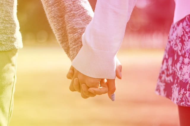 男性が一緒にいて落ち着く女性と手を繋いでる様子