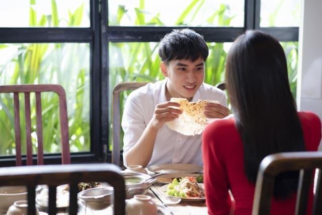 一緒にいて落ち着く女性と食事している男性の笑顔