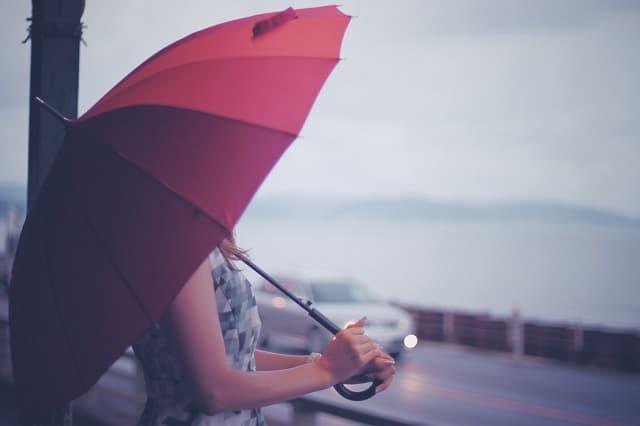別れたばかりの女性が雨の中、海を見ている様子