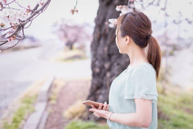 片思いから両想いなったかもしれないと思う女性が不安な様子で携帯を見つめる姿