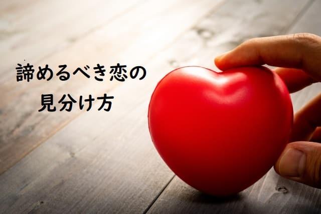 諦めるべき恋の見分け方を解説する男性の手とハートの置物